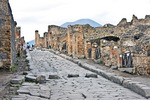 Ancient Roman city of Pompeii, ruins of buildings and Via Stabiana street of basalt paving stones with elevated pedestrian crossing stones, with Mount Vesuvius in background