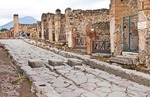 Ancient Roman city of Pompeii, ruins of buildings and Via Stabiana street of basalt paving stones with elevated pedestrian crossing stones and wheel ruts, with Mount Vesuvius in background