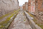 Ancient Roman city of Pompeii, narrow paved stone side street and building ruins