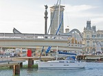 Barcelona's Rambla del Mar pedestrian bridge at Port Vell opening for sailboat to leave Darsena Nacional marina, with Colon Monument and old Port of Barcelona building in background