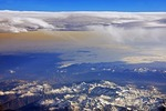 France/Spain border: Snow-capped eastern Pyrenees Mountains of granite and gneissose rock with France at bottom, Spain in middle at right, and Mediterranean Sea at middle on left.  High cirrocumulus clouds are above and low stratus clouds partially cover Mediterranean in distance.
