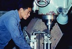 1979 machine shop worker on drill press at factoy at Qinghua University in Beijing