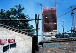 1988 construction of Beijing's World Trade Centre contrasts with old Eastern District neighborhood housing being removed