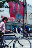 Bicyclists pass a billboard of Mao Zedong and his temporary successor as Communinst Party Chairman, Hua Guofeng, in the Chengdu, Sichuan, city center in 1979