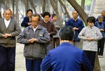 Group practicing qigong, a meditative exercise of slow movement and controlled breathing, in a Xi'an park.  Large group practice of qigong was banned in China in 1999 due to influence of the Falun Gong cult which politicized the practice.