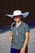 1980s Chinese womens ubiquitous summer fashion favorite was a folding nylon sun hat as worn by a young women on Beijing's Changan Avenue in 1982