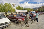 Young Tibetan men inspecting used cars, including foreign models, for sale by Tibetan automobile dealership in public square near Potala Palace in Lhasa in 1997