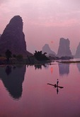 Sunrise on Jade Dragon River, tributary of the Li River, with man on bamboo raft near Yangshuo (Guilin area) in Guangxi