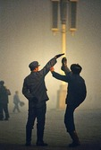 Peoples Liberation Army (PLA) soldiers at horseplay high kicking in Tiananmen Square in Beijing on foggy morning in 1979.