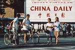 Beijingers on downtown Changan Boulevard in front of billboard announcing China's first, and only, national newspaper in English, the China Daily, in 1981.