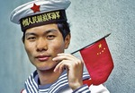 Chinese Navy sailor holding national flag on the Shanghai docks of Huangpu River in 1983