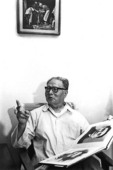 Wu Yinxian, father of Chinese photojournalism, in his Beijing home in 1982 holding copy of his collected works that include his photos of Communist Chinese leaders Mao Zedong, Zhou Enlai, General Zhu De, and Deng Xiaoping from revolutionary Yenan base, plus his famous image of Canadian Doctor Norman Bethune operating during Anti-Japanese War above on wall.