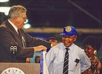 Nelson Mandela, with Winnie Mandela in back, being given a cap and jacket by UAW president Owen Bieber at Ford plant in Dearborn, Michigan, in 1990, during U.S. tour.