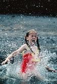Girl splashing in water at Lake Erie beach