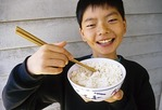 Chinese boy eating with chopsticks from rice bowl