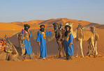 Tuareg men with dromedary camels at sunset in Sahara sand dunes of Erg Chebbi near Merzouga, Morocco
