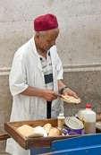 Food vendor slicing Tunisian bread in Souk El Kachachine of the Old Town Tunis Medina