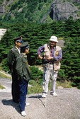 Chinese-American tourist photographer chatting with local police at Huangshan National Park