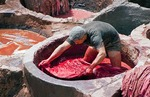 Worker in red dye vat dyeing animal hide to be made into slippers (babouche) at famous tanneries of Fes, Morocco.
