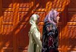 Muslim women passing carved door in old medina of Fes, Morocco