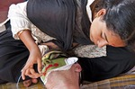 An expert artist specializing in Kathakali make-up draws the design and applies the curved white rice-paste beard on the actor, in this case an Italian student, who lies on his back during the process which lasts from 3-4 hours.