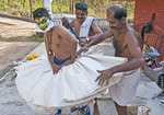 Kathakali actor being fitted with his costume.  20 to 40 pieces of stiff cloth made from rice sacks are wrapped tightly with a long twisted rope to form an oval shaped frame to fit under a skirt.