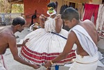 Kathakali actor being fitted with his costume.