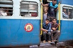 Young men viewing countryside from a moving intercity Indian Railways passenger train in Kerala.