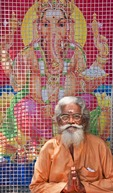Sadhu or holy man in front of poster of Hindu god Ganesh in Kerala's capital of Trivandrum.