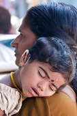 Mother carrying sleeping daughter wearing hearing aide in Kerala's capital of Trivandrum.