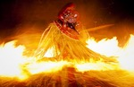 Rapidly spinning Theyyam performer surrounded by flaming torches dances a variation of the fire ritual performed at festivals in North Kerala.