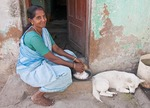 Woman shredding coconut on stoop of her residence in Kanyakumari Beach neighborhood.