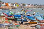 Fishermen on Kanyakumari Beach waterfront preparing boats.