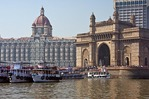 Boats in harbour in front of Mumbai's The Taj Mahal Palace Hotel and Tower at Gate of India built in 1903.