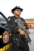 Guatemala National Civil Police officer with automatic weapon near Honduras border on patrol for drug and immigration trafficking