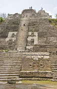 "Yucatec Maya Mesoamerican archaeological site of Lamanai (""submerged crocodile"") with tourists climbing stairway of the High Temple"