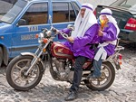 Holy Week (Semana Santa) penitents wearing purple rebes, arriving in Antigua by motorcycle, to participate as cucuruchos in the annual religious processions