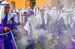 Holy Week (Semana Santa) penitents in Antigua fill the street with smoke from their swinging lanterns while participating as cucuruchos in the annual religious processions