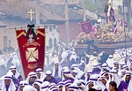 Holy Week (Semana Santa) penitents in Antigua wearing purple rebes participating as cucuruchos in the annual religious processions of floats