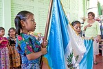 Teacher leading kindergartner class of Mayan children in pledge of allegiance to Guatemalan flag in village school near Antigua.