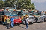 "Guatemalan ""chicken bus"" drivers waiting for passengers in Antigua bus parking lot."