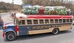 "A fully loaded Guatemalan ""chicken bus"" transporting passengers and agricultural produce from the countryside into Antigua."