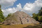 Tourists climbing temple of Mayan ruin of Yaxha