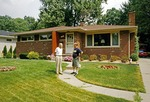 Retired homeowner and neighbor in front of modest house in Ann Arbor, Michigan, USA