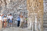 Local guide with tourists describing Maya calendar on stele at Mayan ruin of Copan