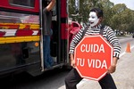 "Mime on Guatemala City street with ""Take Care of Your Life"" (Cuida tu Vida) sign promoting highway safety in cooperation with police"