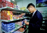 Beijing, China, shopper looking at American brand tooth paste in grocery.