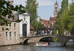 Bruges (Brugge) canal with swan and tourist cruise boat at bridge and gate to  Beguinage (Prinselijke Begijnhof van Wijngaerde) women's residence of the Beguines