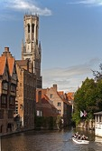 Medieval architecture of Bruges (Brugge) is dominated by the Belfort (belfry tower) as seen across canal from Dijver in city's historic center