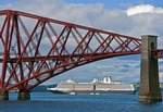 Holland America Line's Eurodam cruise ship anchored in Scotland's Firth of Forth framed by a section of the iconic 19th century cantilevered Forth Railway Bridge.